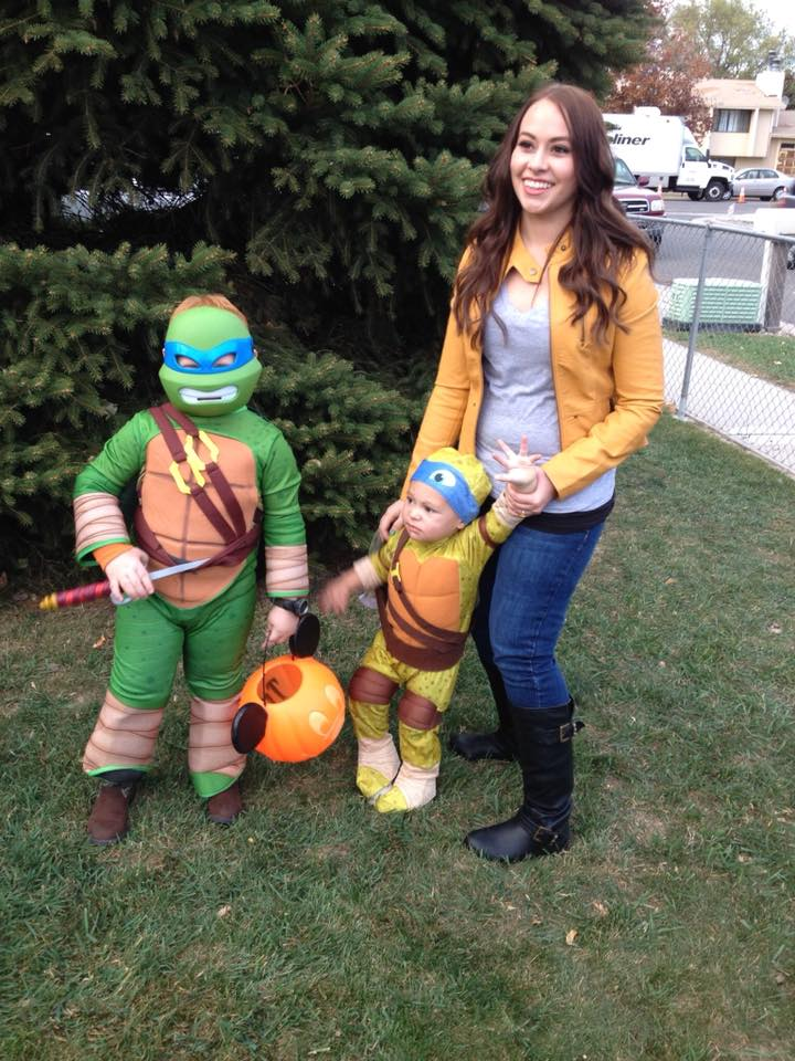 Family wearing TMNT Halloween costumes smiles in front of green pine tree.