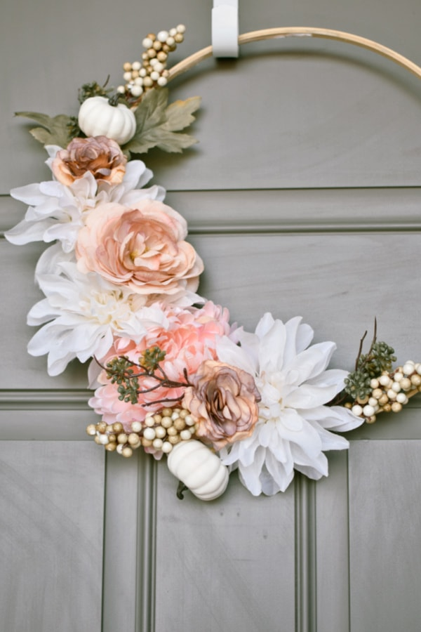 Embroidery hoop wreath with pink and cream flowers, white pumpkins, and green leaves on gray door.