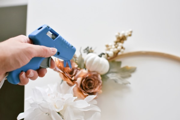 Woman holds hot glue gun above faux fall flowers and wooden embroidery hoop.