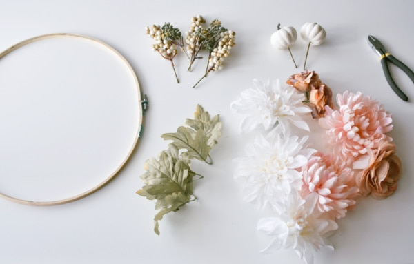 Wooden embroidery hoop and pink and cream faux flowers on white table.