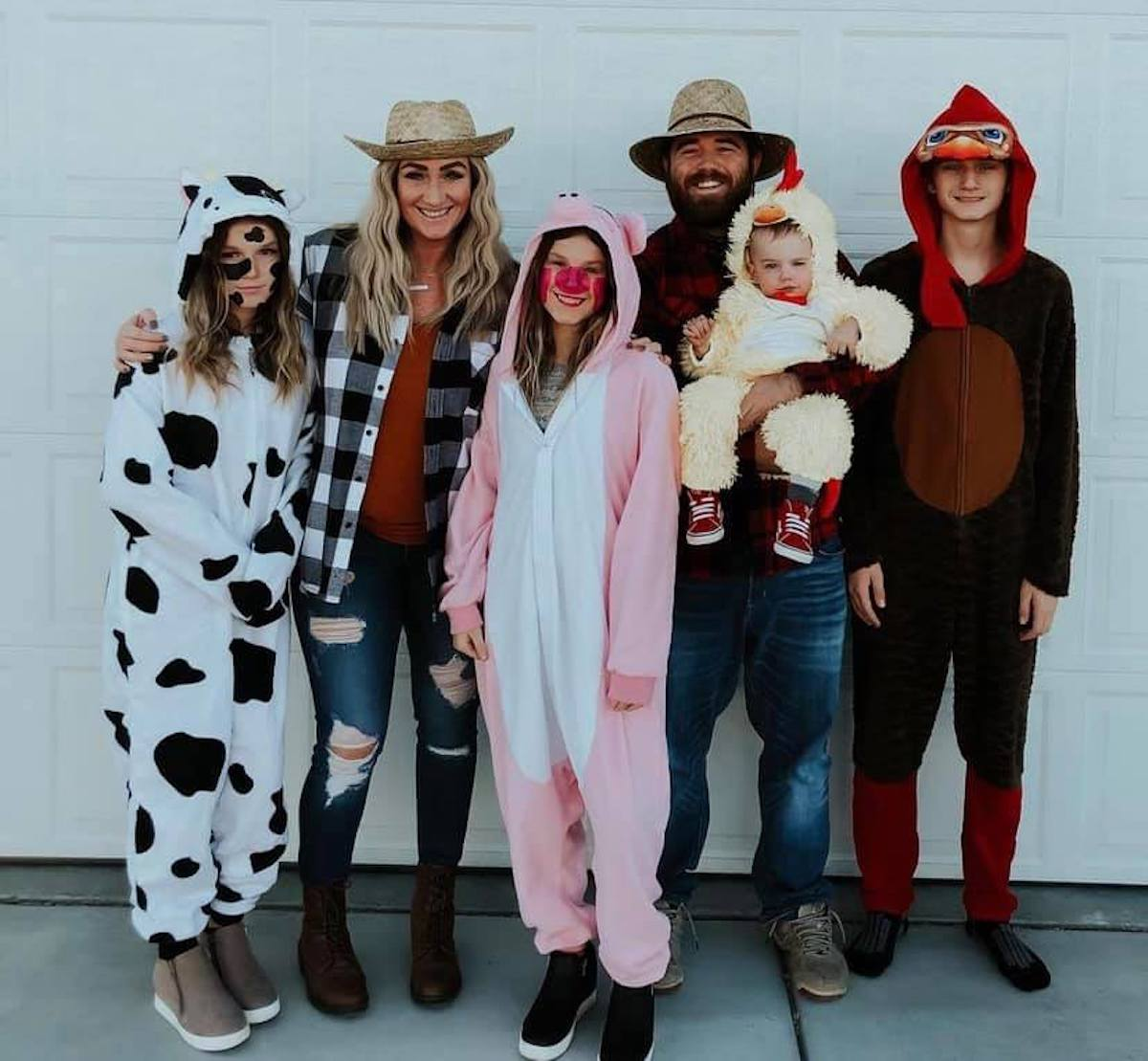 Man and woman dressed as farmers surrounded by teenagers and baby wearing animal costumes.