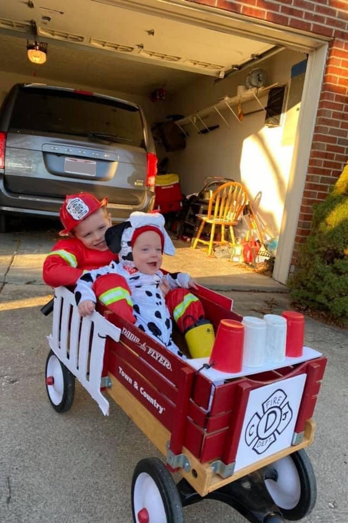 Boy dresses as fireman and baby dressed as dalmatian sit in DIY wagon firetruck.