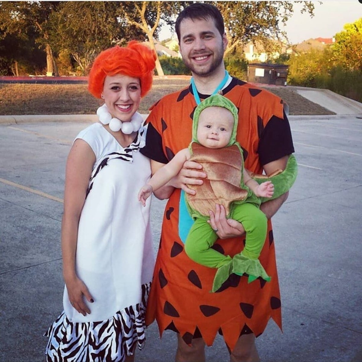 Family wearing Flinstones costume stands by each other and smiles.