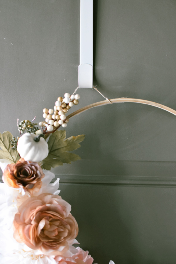 Close up of fall wooden hoop wreath with pink and cream faux flowers on white wreath hook.