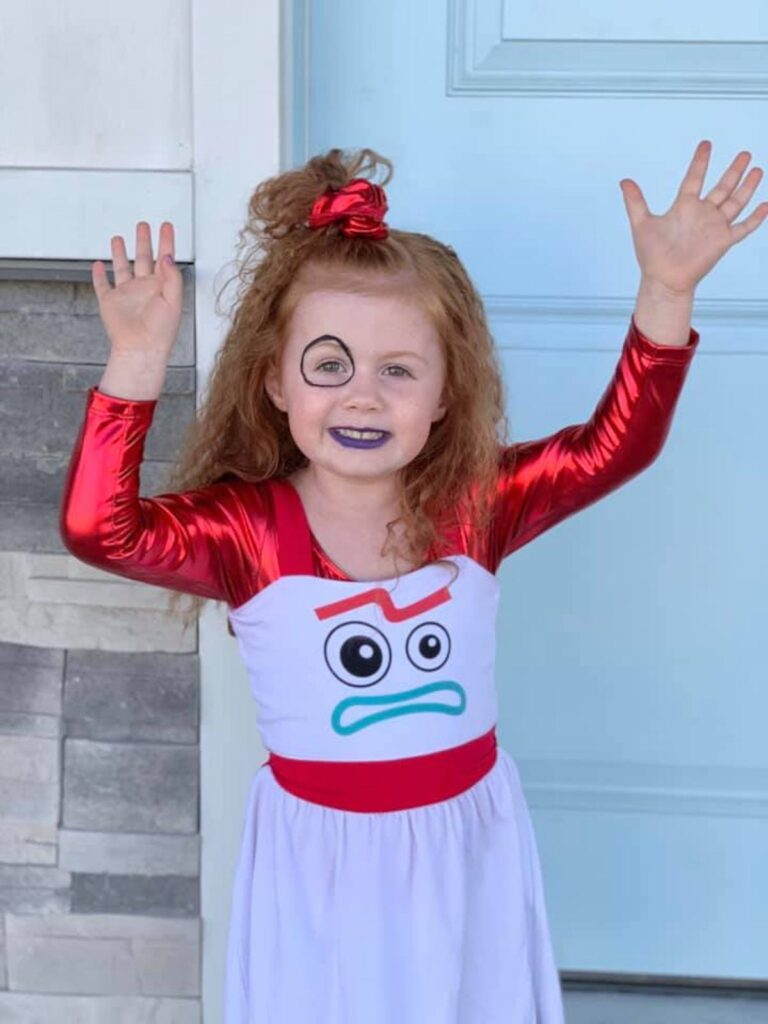Red haired girl wearing Forky costume puts hands in air and smiles.