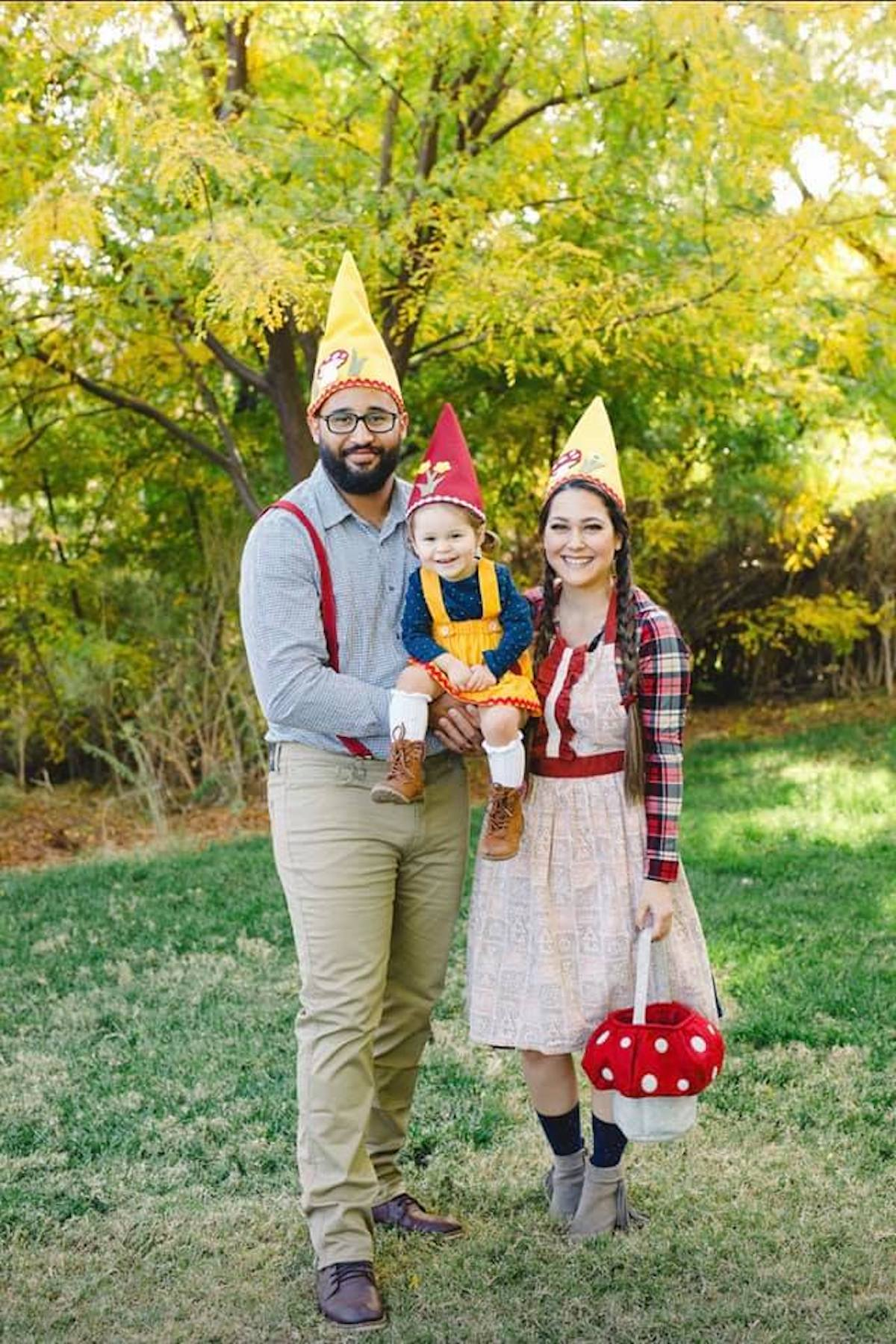 Family wearing gnome costumes stands in grass area and smiles.