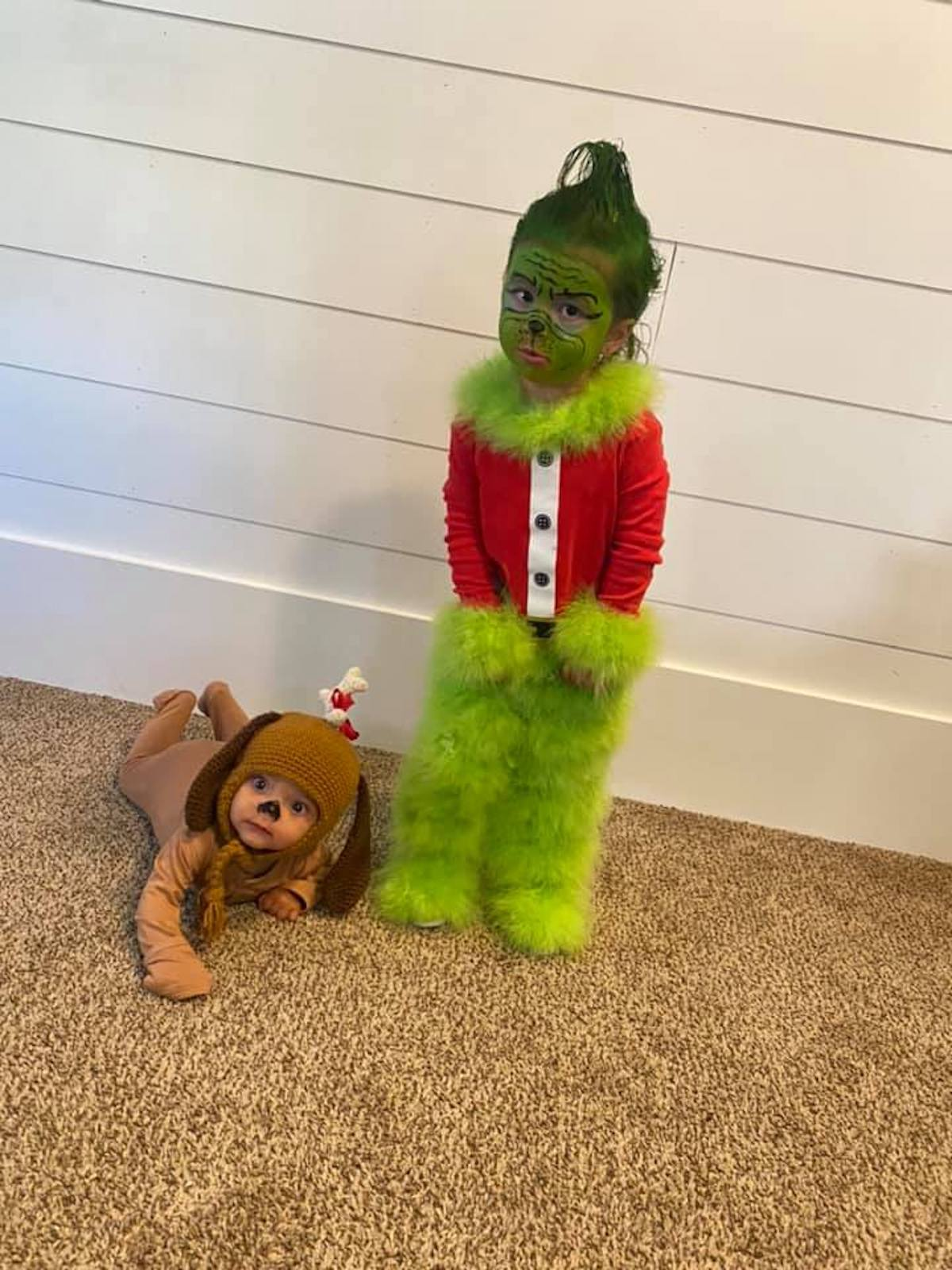 Boy wearing Grinch costume and baby wearing Max costume stand in front of white wall.
