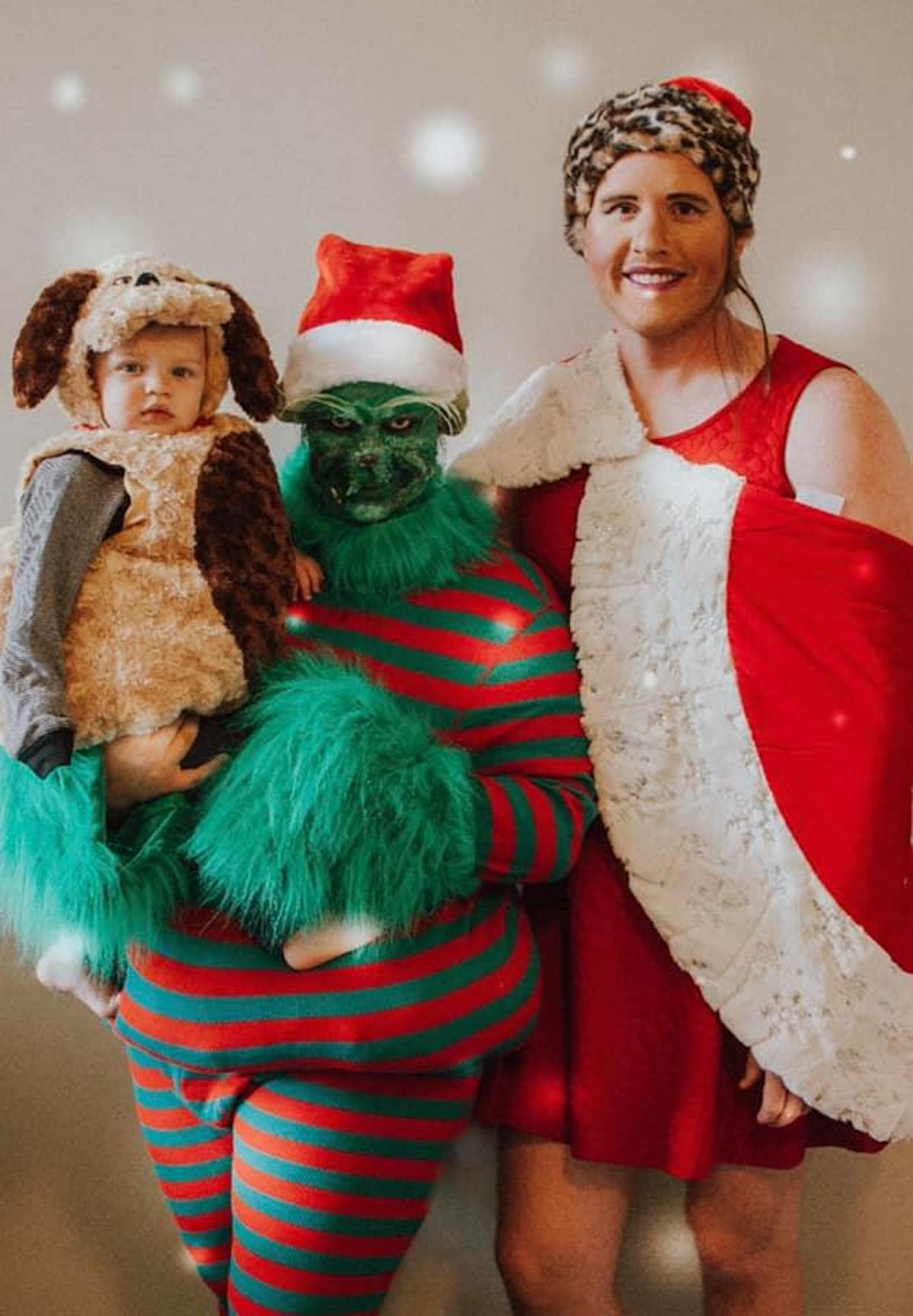 Family wearing character costumes from The Grinch smile for picture.