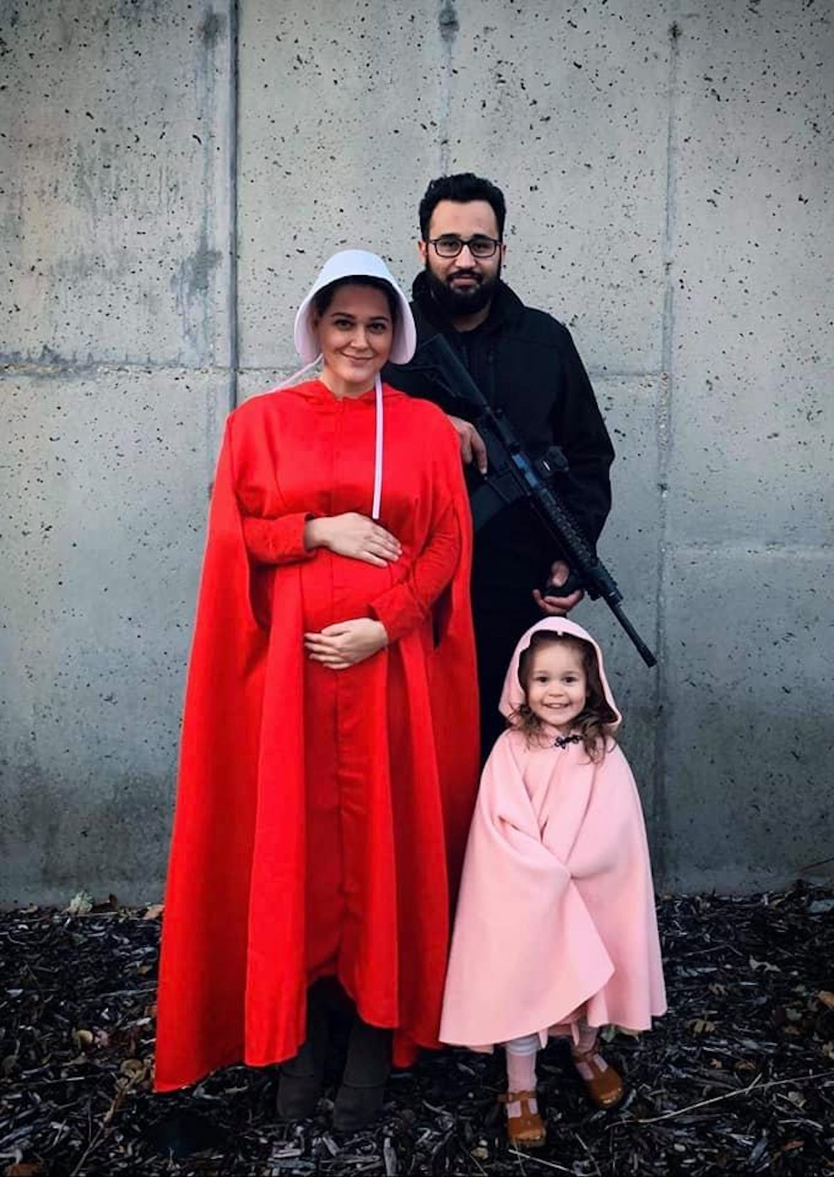 Family dressed as Handmaid's Tale stands in front of cement wall and smiles.