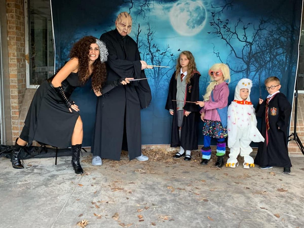 Family wearing Harry Potter costumes poses in front of photo backdrop.
