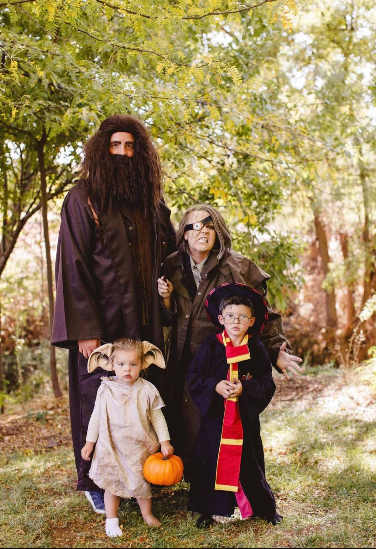 Family wearing Harry Potter costumes poses in front of trees.