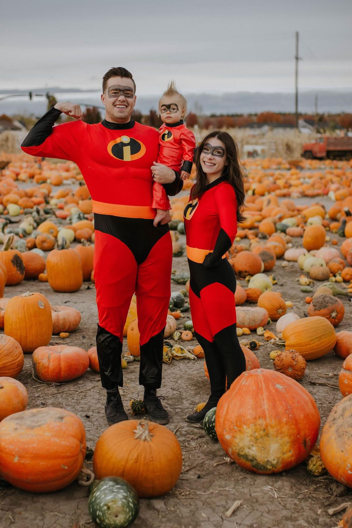 Family wearing Incredibles costumes poses in pumpkin patch.