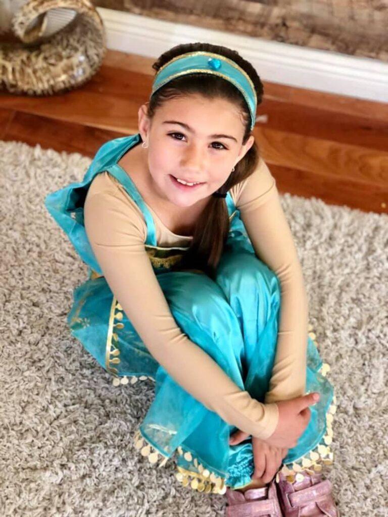 Girl wearing Jasmine costume sits on floor and hugs her legs.