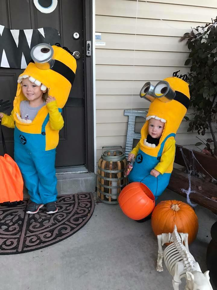 Brother and sister wearing Minion kids Halloween costumes smile on porch with candy buckets.