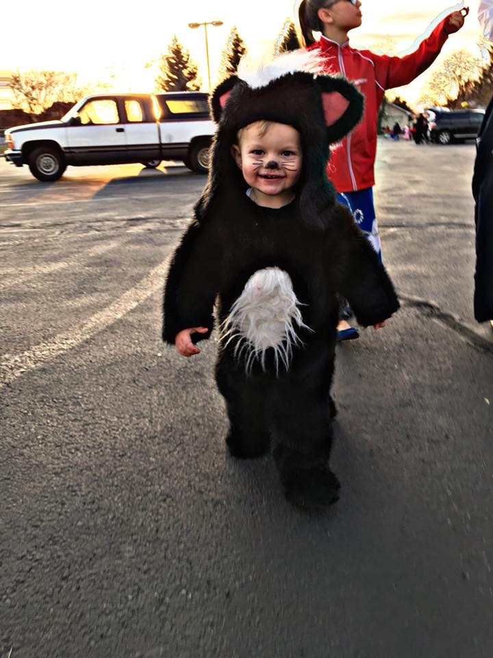 Little boy smiles in parking lot while wearing skunk Halloween costume.