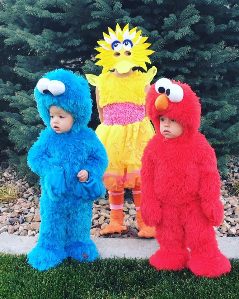 Three siblings wearing Sesame Street kids Halloween costumes stand in front of pine tree.
