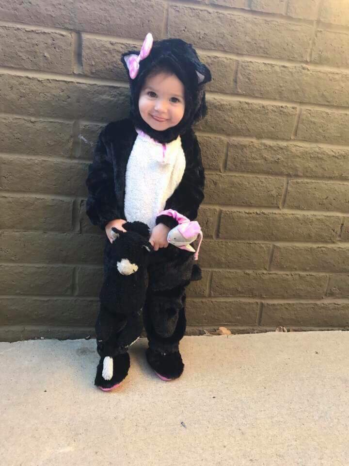 Little girl wears cat Halloween costume and smiles next to brick wall.