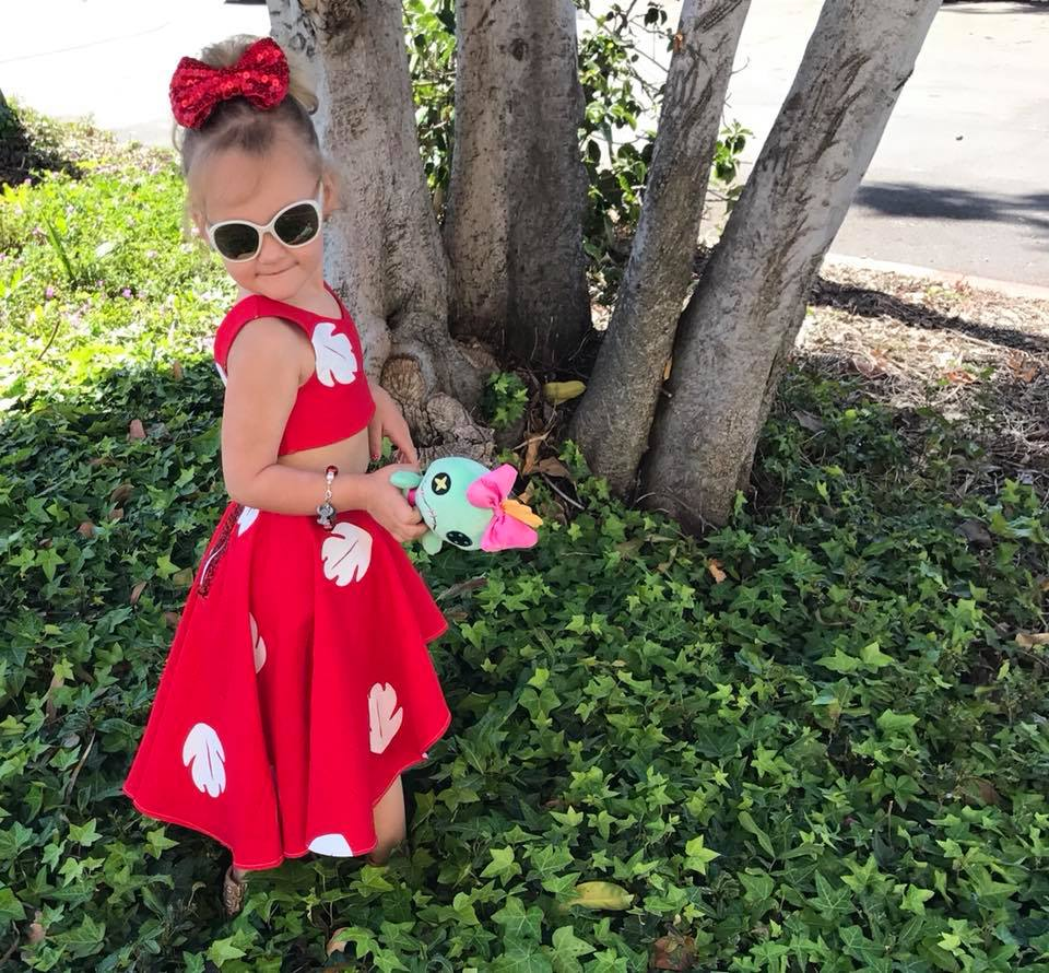 Girl wears Lilo kids Halloween costume and holds stuffed animal while standing in leaves.