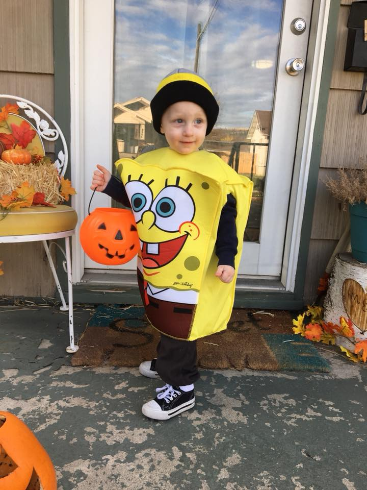 Boy wearing Spongebob kids Halloween costume holds candy bucket and stands on decorated porch.