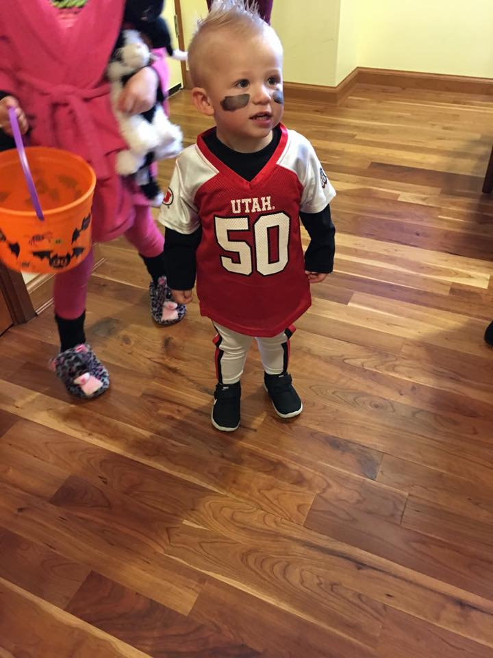 Toddler boy wearing football player kids Halloween costume stands in living room.
