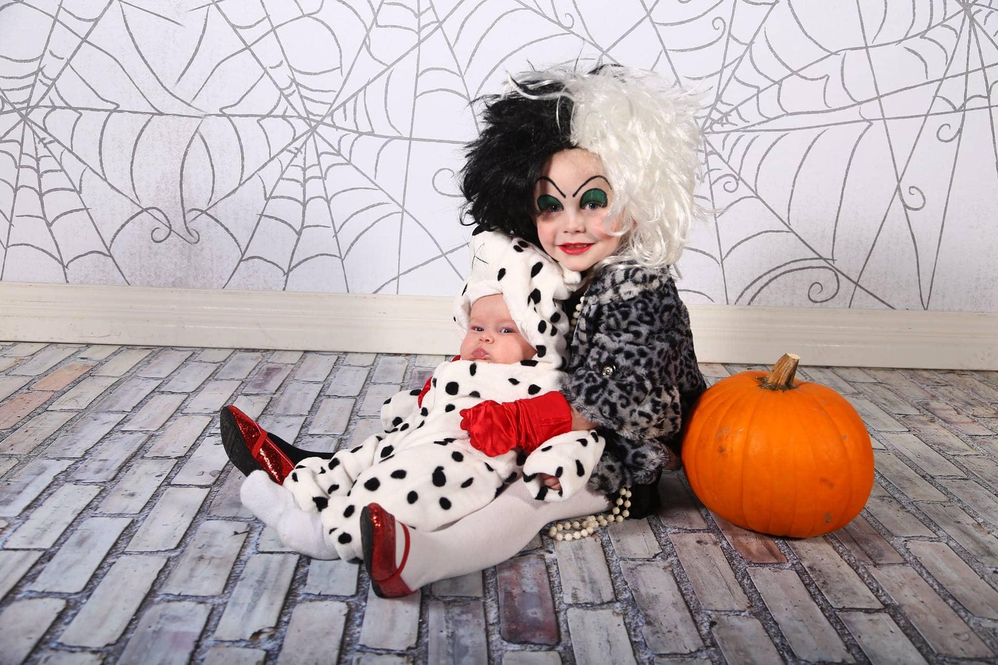 Girl wearing Cruella DeVil kids Halloween costume holds baby wearing dalmatian costume.