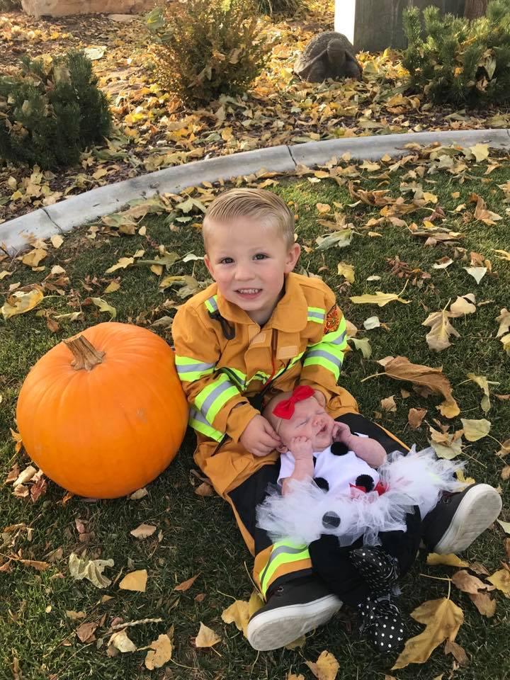 Brother wearing fireman kids Halloween costume holds sister wearing dalmatian costume.