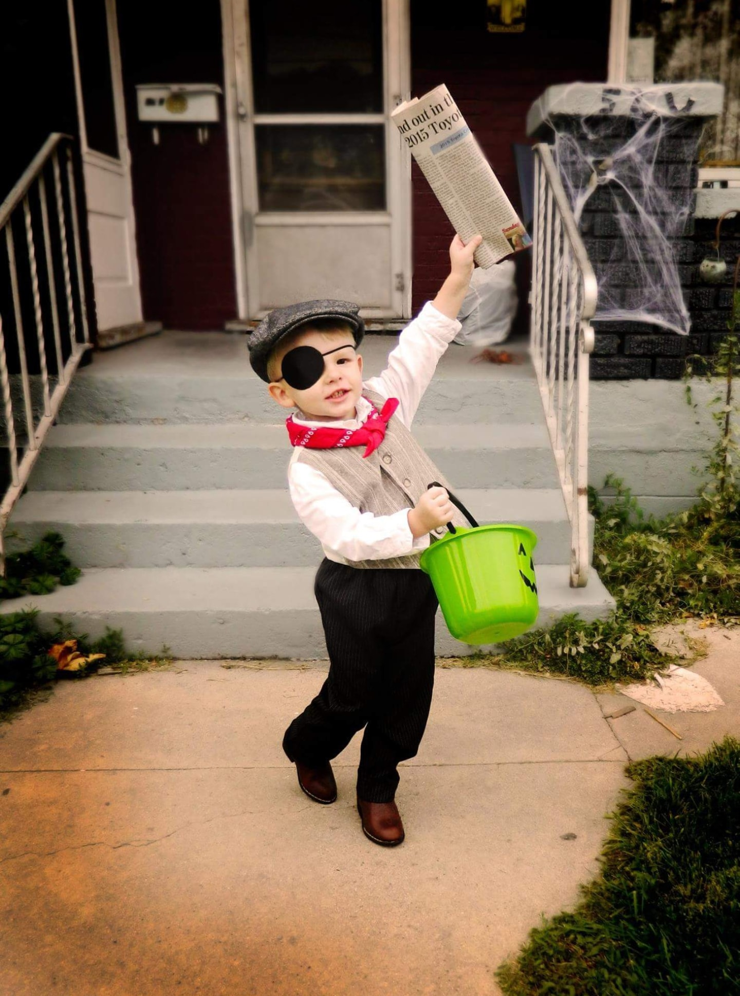 Boy wearing Newsies kids Halloween costume holds candy bucket and newspaper in the air.