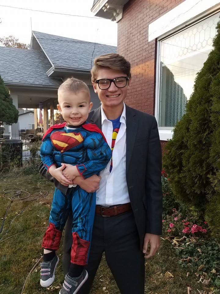 Teenager wearing Clark Kent costume holds baby boy wearing Superman costume.