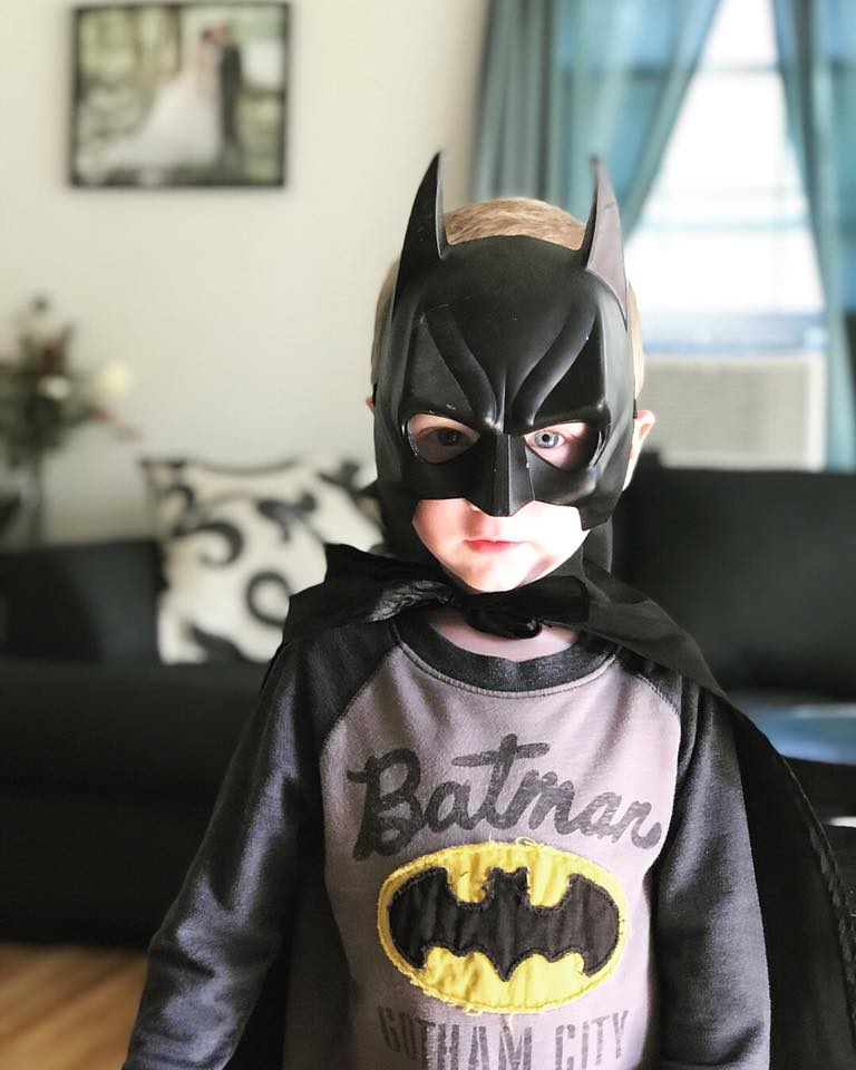 Close up photo of boy wearing Batman kids Halloween costume with living room in background.