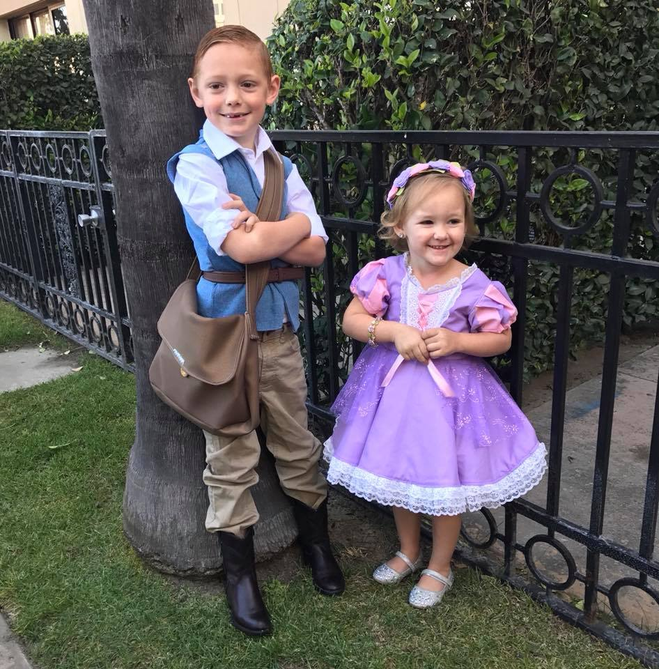 Brother and sister dressed as Rapunzel and Flynn Rider smile next to tree and black gate.