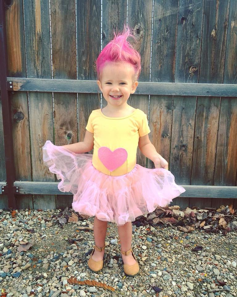 Girl wearing DIY troll Halloween costume smiles and holds her skirt out.