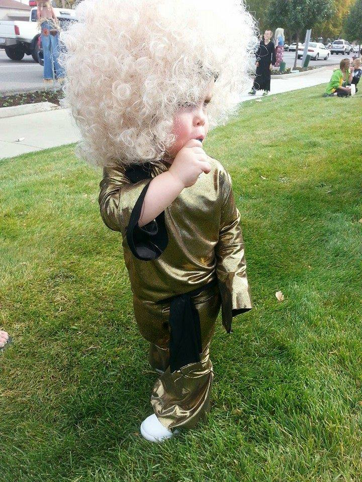Girl wearing wig and Disco queen kids Halloween costume holds sucker in mouth.