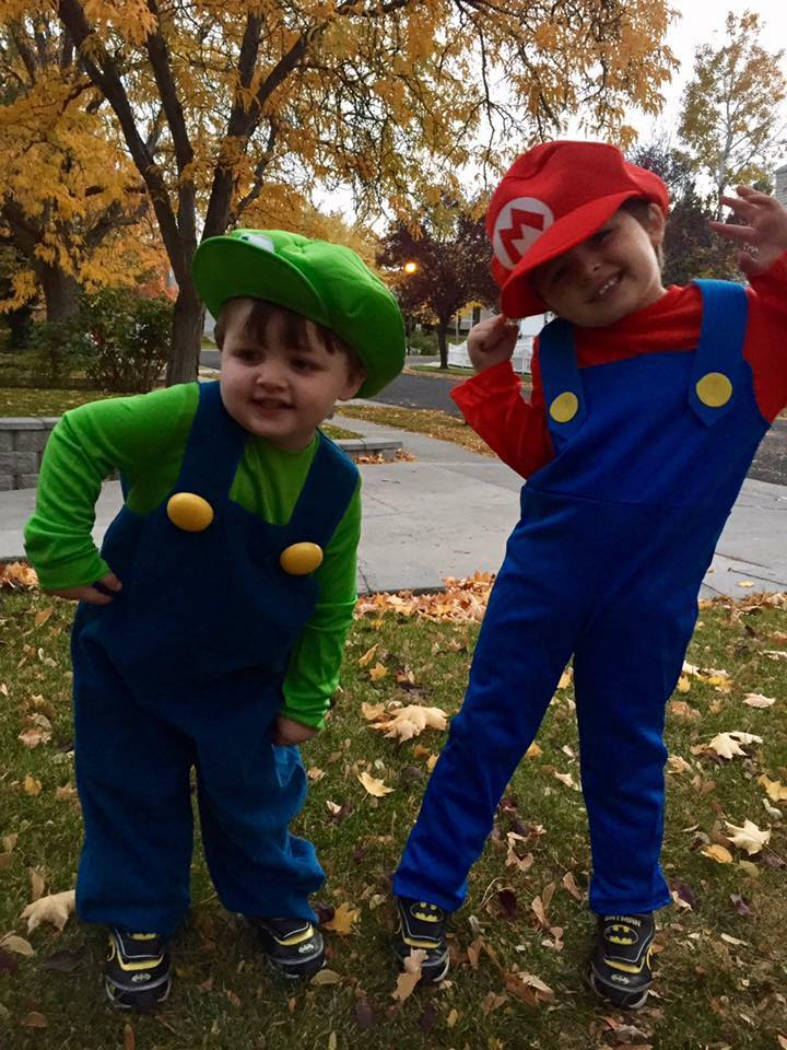 Two brothers wearing Mario and Luigi kids Halloween costumes make silly faces.