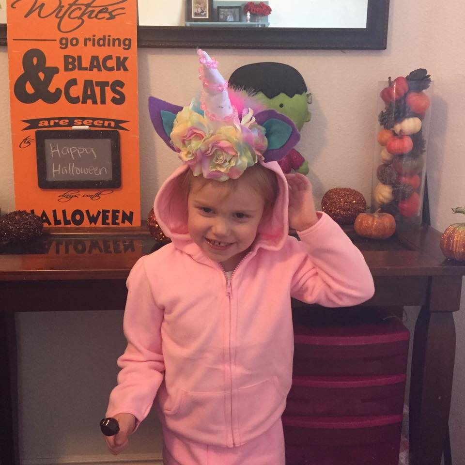 Girl wearing DIY unicorn costume touches her head with one hand and holds a sucker with other.