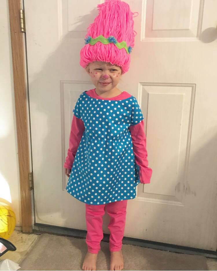 Little girl squints her eyes while wearing DIY Princess Poppy Halloween costume.