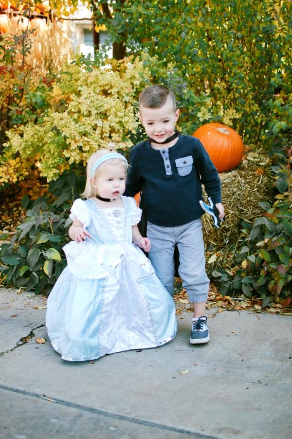 Boy wearing prince costume stands next to girl wearing Cinderella kids Halloween costume.