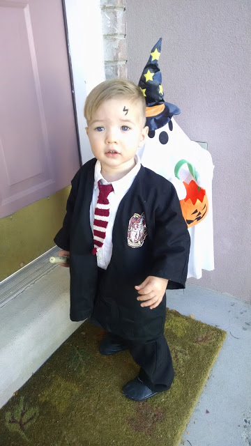 Baby boy wearing DIY Harry Potter Halloween costume stands on porch with decorations.