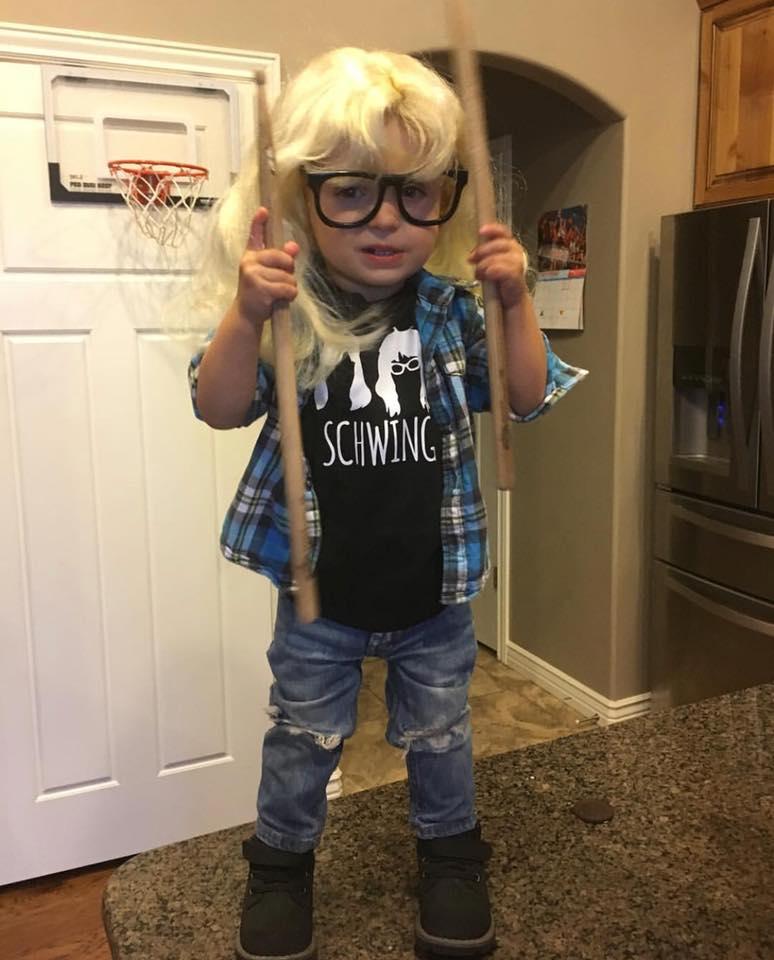 Boy wearing Wayne's World kids Halloween costume holds drum sticks while standing on counter.