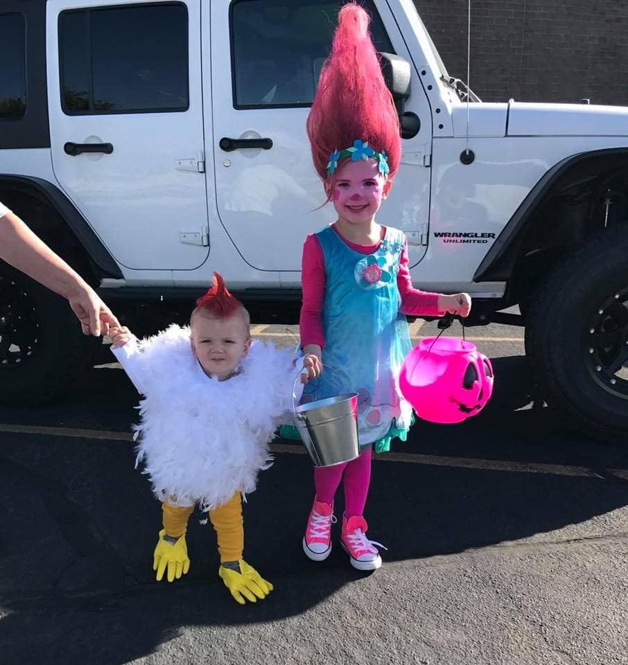 Girl wearing Princess Poppy Halloween costume holds hands with baby boy wearing chicken costume.