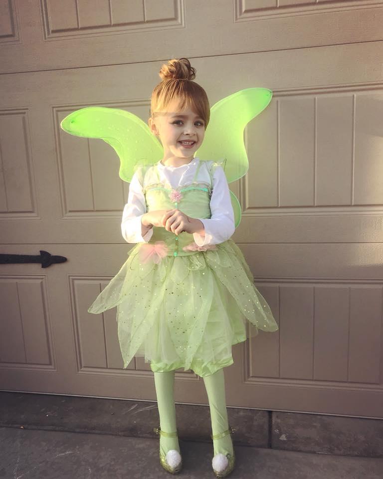 Girl smiles in front of garage door while wearing Tinkerbell Halloween costume.