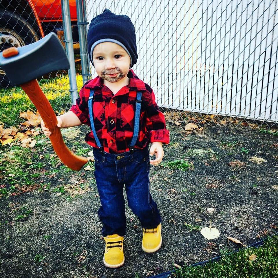 Toddler boy wearing lumberjack kids Halloween costume holds pretend ax.