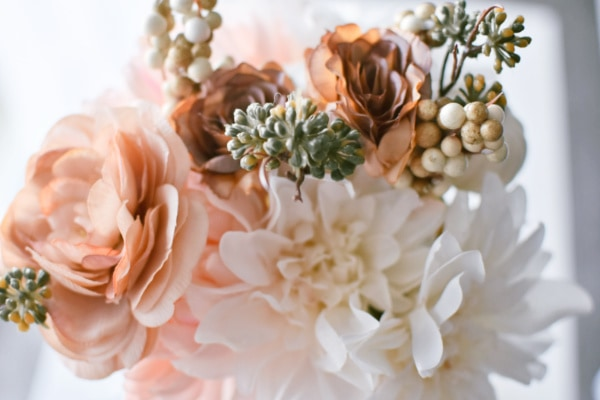 Close up photo of pink and cream faux fall flower bunch.