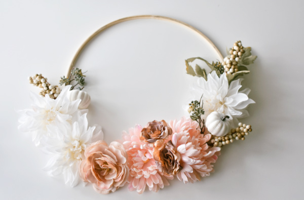 Embroidery hoop with pink and cream faux flowers placed on it on white table.