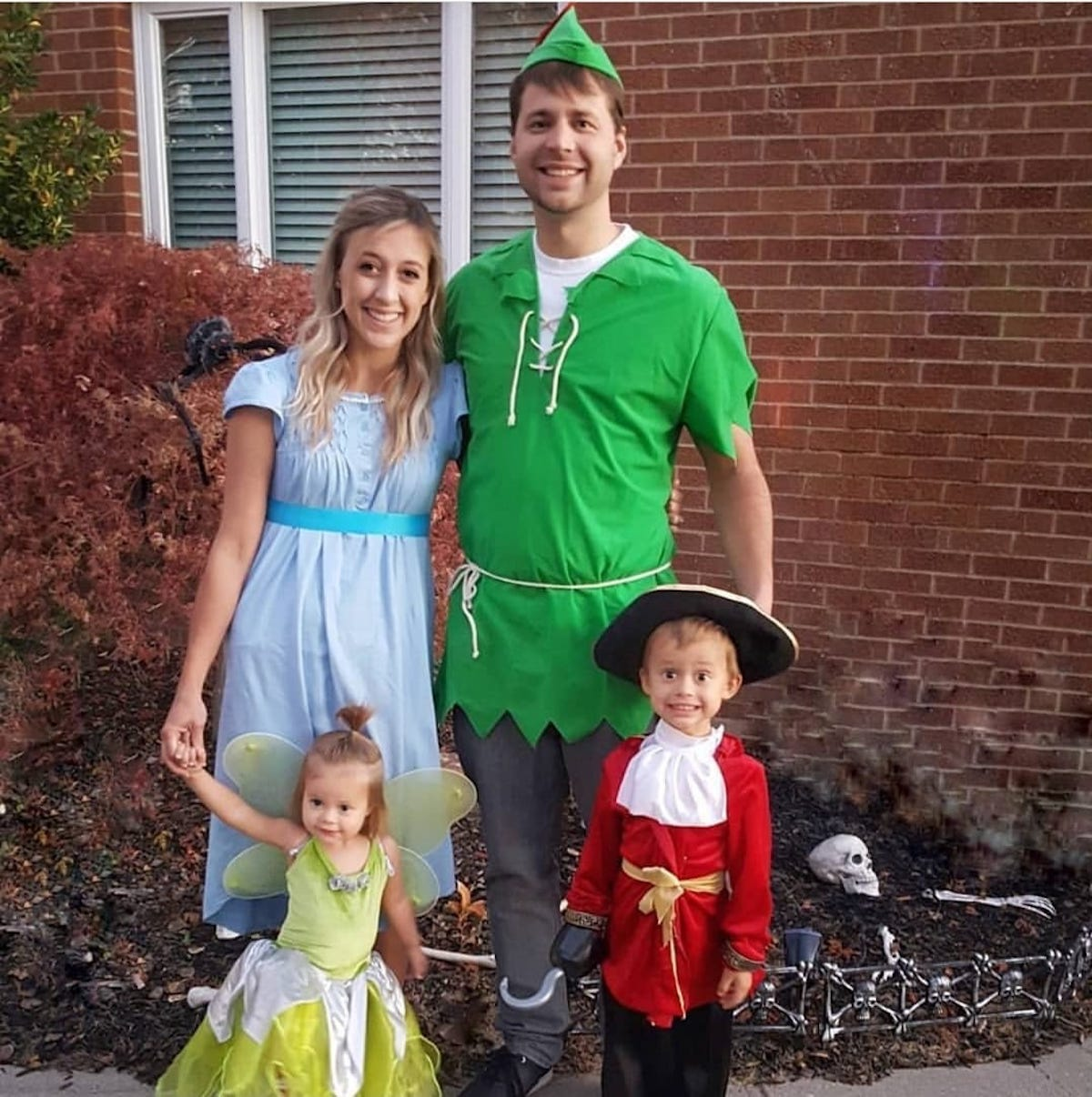 Family wearing Peter Pan character costumes smiles in front of red brick house.