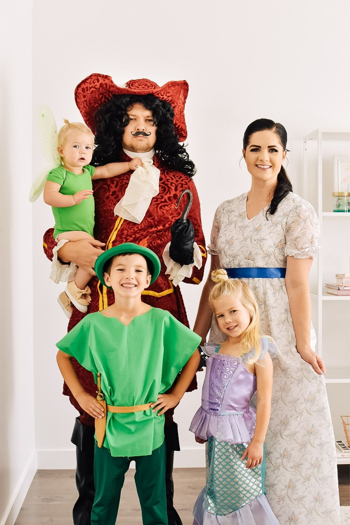 Family wearing Peter Pan character costumes smiles in front of white wall.