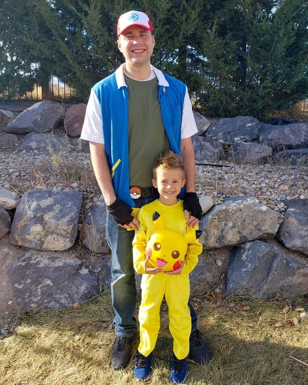 Man wearing Ash Ketchum costume stands behind boy wearing Pikachu costume.