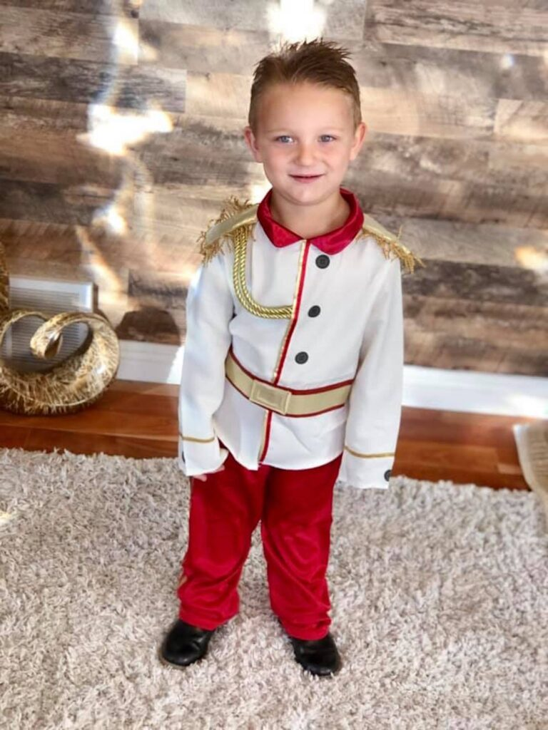 Boy wearing Prince Charming costume smiles in living room.