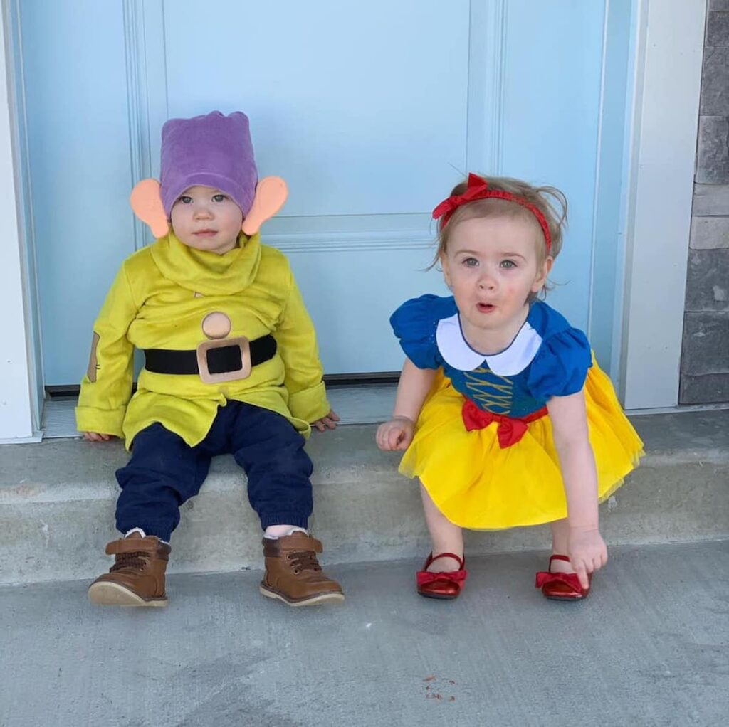 Baby boy wearing Dopey costume and baby girl wearing Snow White Costume sit in front of blue door.