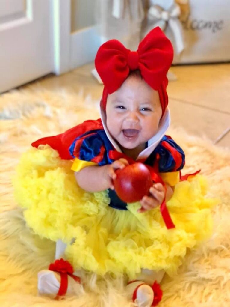 Baby wearing Snow White costume and holding apple smiles while sitting on floor.