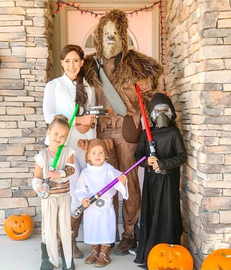 Family wearing Star Wars costumes smile on front porch with pumpkins.